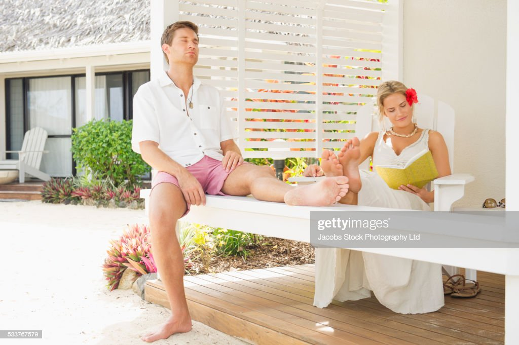 Caucasian couple relaxing on porch railing : Foto stock