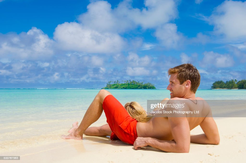 Caucasian couple relaxing on tropical beach : Foto stock