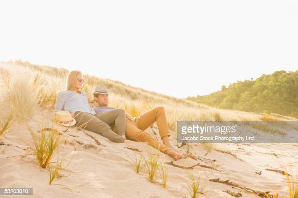 caucasian couple relaxing together on beach - whangarei heads stock-fotos und bilder