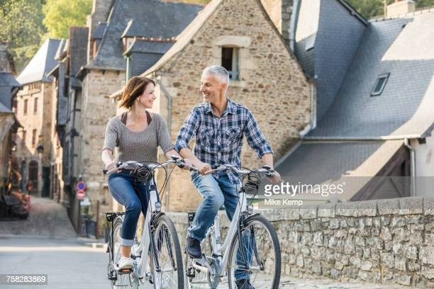 Caucasian couple riding bicycles in city