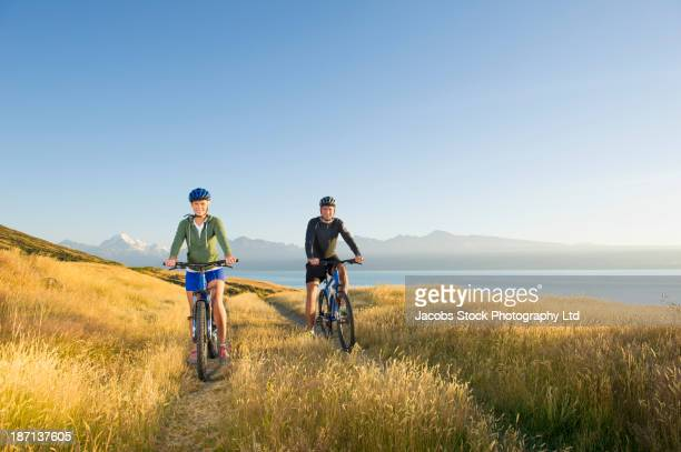 Caucasian couple riding bicycles in rural field