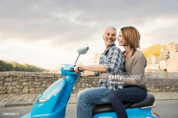 caucasian couple riding blue motor scooter - 40 49 jaar stockfoto's en -beelden
