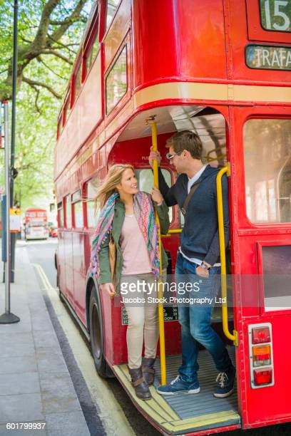caucasian couple riding double decker bus, london, middlesex, united kingdom - double decker bus stock pictures, royalty-free photos & images
