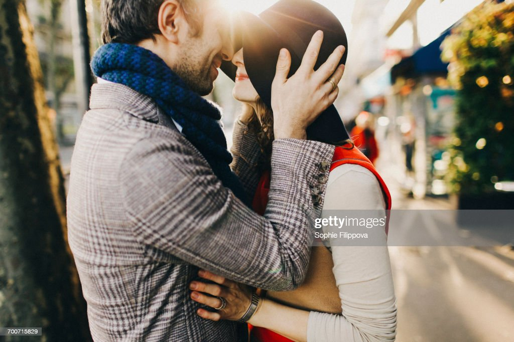Caucasian couple rubbing noses on sunny day : Stock Photo