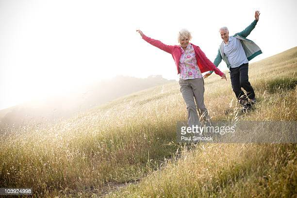 Caucasian couple running down hill