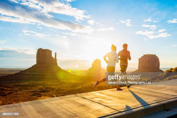 Caucasian couple running in Monument Valley, Utah, United States