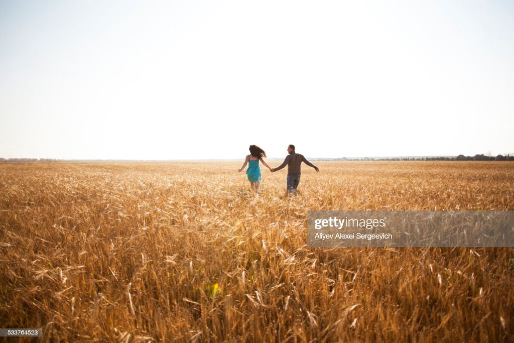 Caucasian couple running in rural field : Foto stock