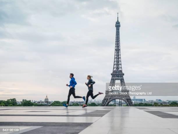 Caucasian couple running near Eiffel Tower, Paris, France