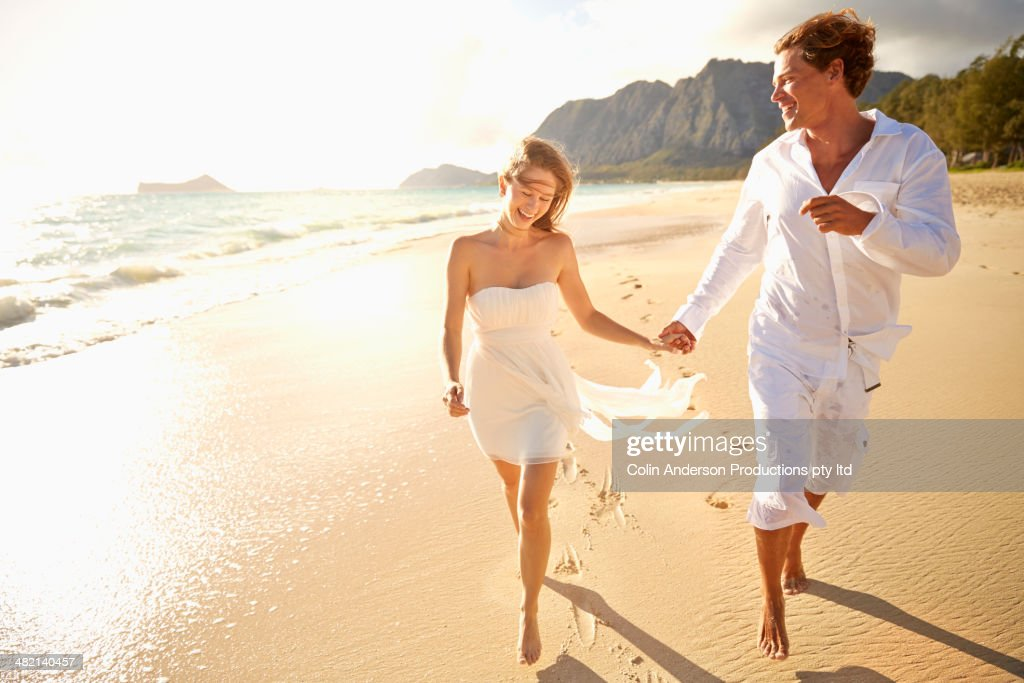 Caucasian couple running on beach : Stock Photo