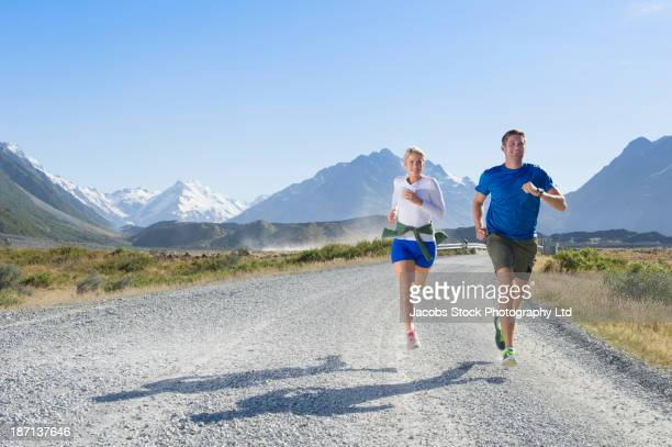 Caucasian couple running on rural road