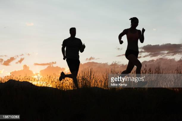Caucasian couple running together at sunset