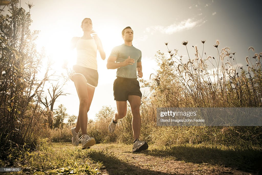 Caucasian couple running together on path : Stock Photo