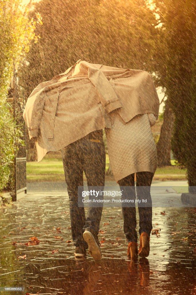 Caucasian couple running under coat in rain : Stock Photo