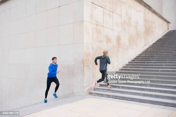 Caucasian couple running up staircase