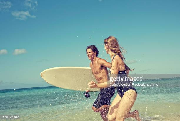 Caucasian couple running with surfboard on beach