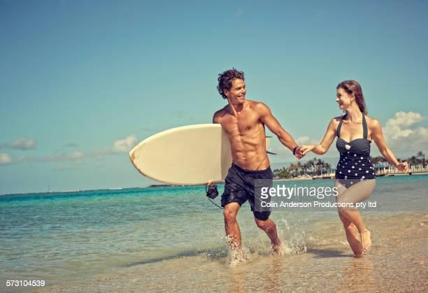 Caucasian couple running with surfboard on beach