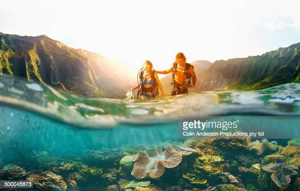 Caucasian couple scuba diving in tropical reef