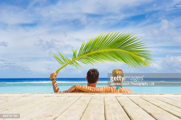 Caucasian couple shading themselves under palm frond in swimming pool