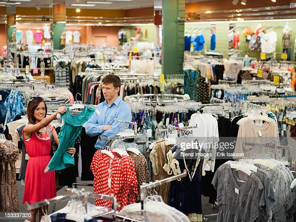 Caucasian couple shopping in clothing store