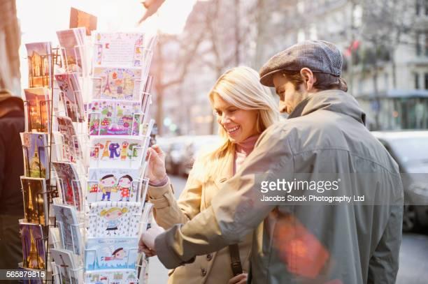 Caucasian couple shopping in sidewalk market
