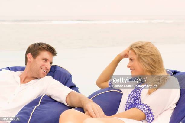 Caucasian couple sitting in beanbag chairs on beach