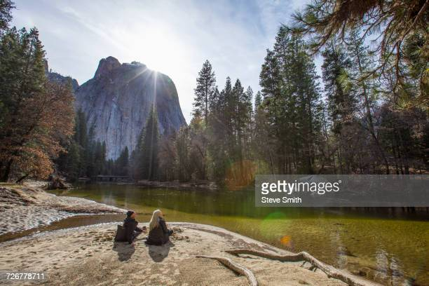 caucasian couple sitting near river - yosemite nationalpark stock pictures, royalty-free photos & images