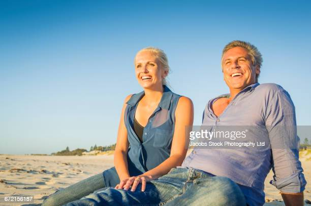 Caucasian couple sitting on beach