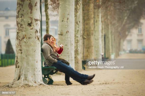 Caucasian couple sitting on bench in park