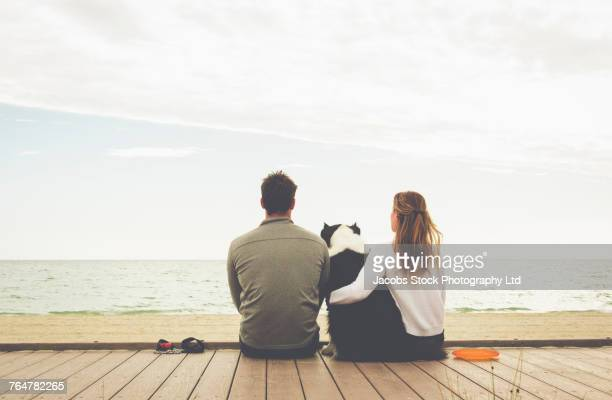 Caucasian couple sitting on boardwalk at beach with dog