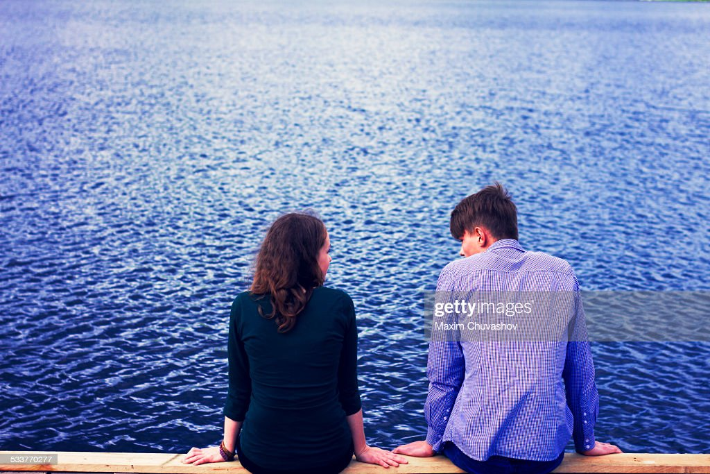 Caucasian couple sitting on dock at lake : Foto stock