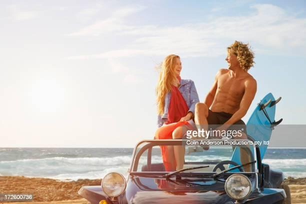 Caucasian couple sitting on jeep on beach