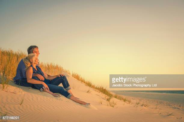 caucasian couple sitting on sand dune at beach - file:myrtle_beach,_south_carolina.jpg stock pictures, royalty-free photos & images