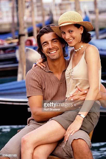 Caucasian couple sitting together near gondolas, Venice, Veneto, Italy