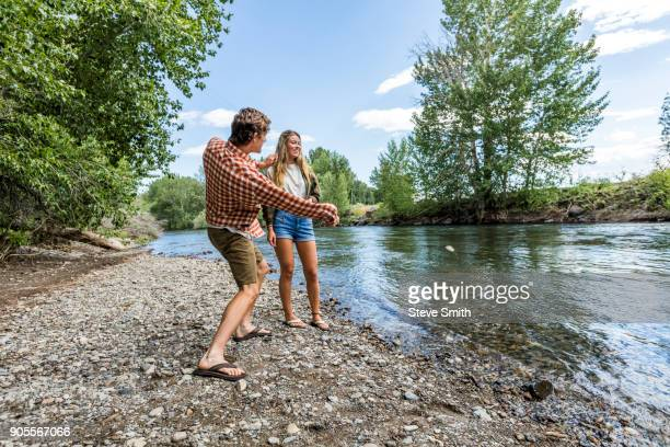 caucasian couple skipping stones in river - skipping along stock pictures, royalty-free photos & images