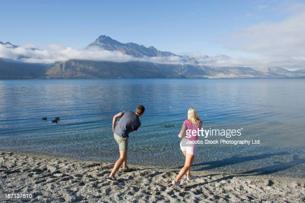 Caucasian couple skipping stones on rural lake