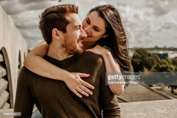 caucasian couple smiling and looking at each other outside,tallinn,estonia - heteroseksueel koppel stockfoto's en -beelden