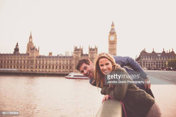 Caucasian couple smiling at clock tower, London, Middlesex, United Kingdom