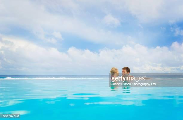 Caucasian couple smiling in swimming pool