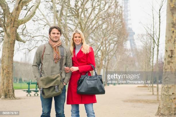 caucasian couple smiling near eiffel tower in park, paris, ile-de-france, france - crossbody bag stock pictures, royalty-free photos & images