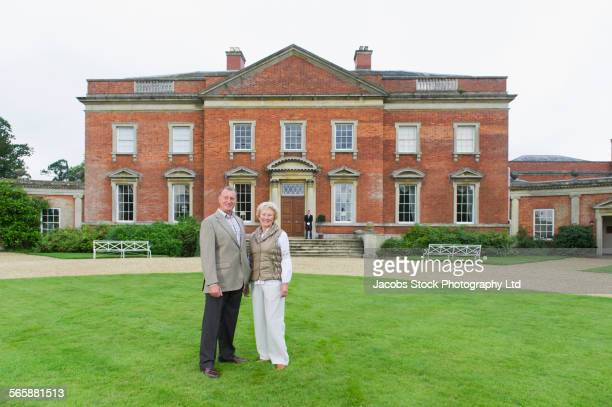Caucasian couple smiling outside mansion