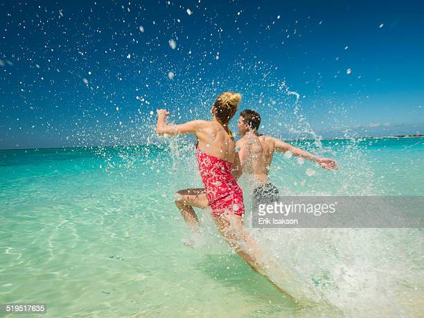 Caucasian couple splashing in waves in tropical ocean