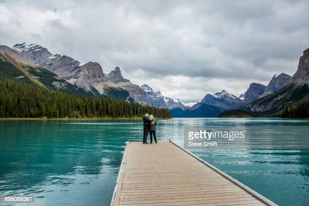 caucasian couple standing at the end of dock on mountain lake - molo foto e immagini stock