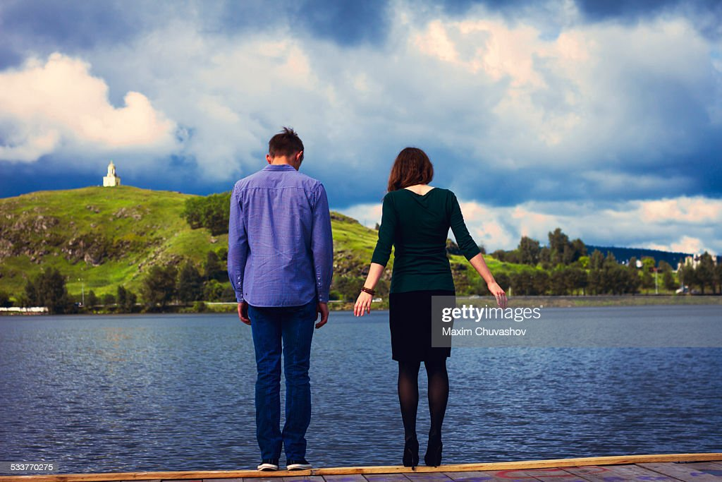 Caucasian couple standing on dock at lake : Foto stock
