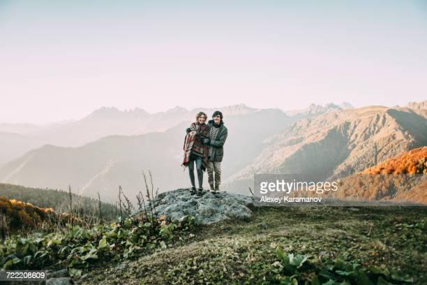 Caucasian couple standing on mountain rock overlooking valley