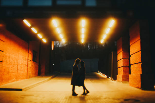 Caucasian couple standing on street in tunnel