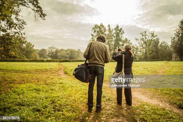 Caucasian couple standing on trail in park with camera
