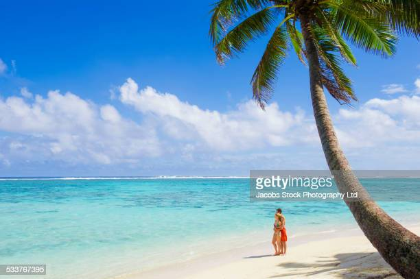 Caucasian couple standing on tropical beach