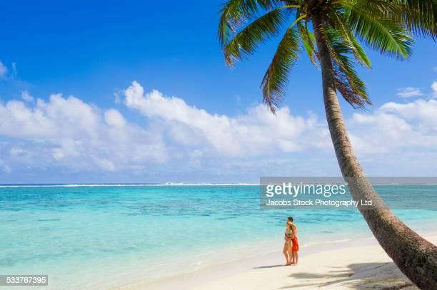caucasian couple standing on tropical beach - isole cook foto e immagini stock