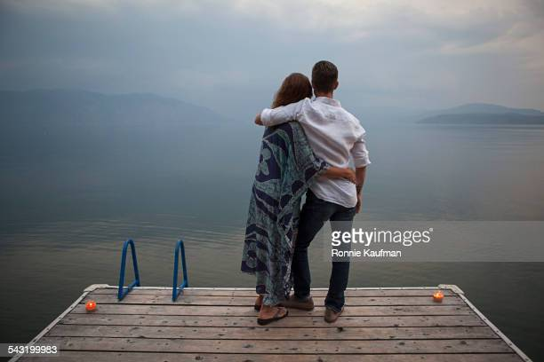 Caucasian couple standing on wooden dock over lake