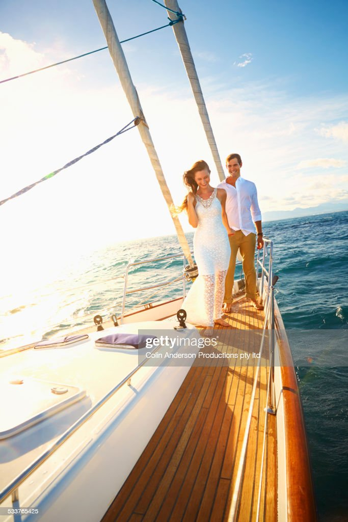 Caucasian couple standing on yacht deck : Foto stock
